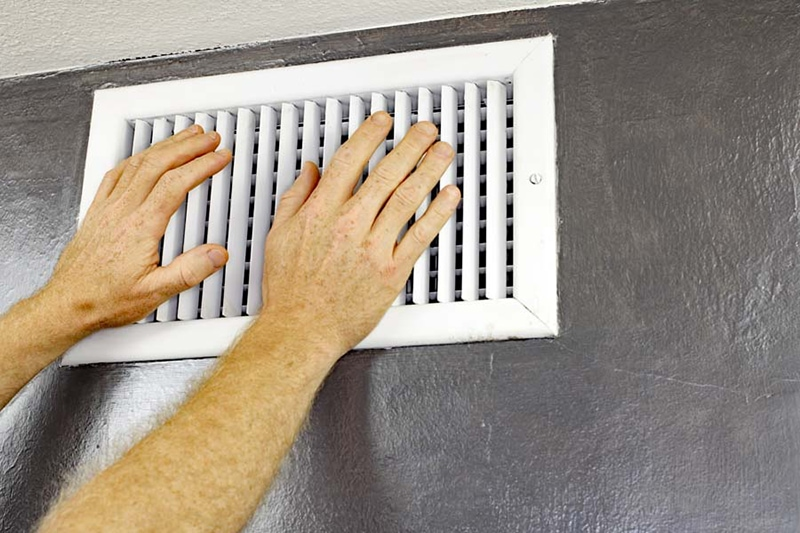 Hands in front of white wall vent
