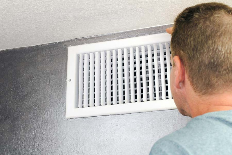man in blue shirt looking at white wall air vent